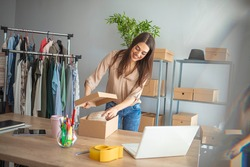 Young woman small business owner working at home office. Online marketing packaging delivery, startup SME entrepreneur or freelance woman concept. Small business owener