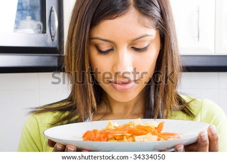 young woman smelling warm food in kitchen