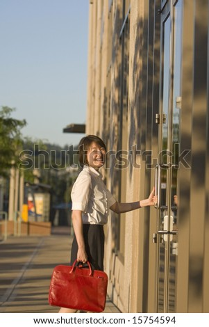 Young woman smiles at camera while opening a door to a building. She is smiling at the camera and carrying a red bag. Vertically framed photo.