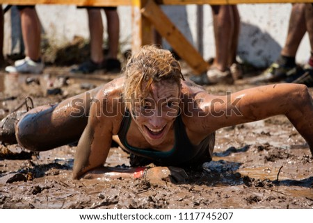 Young woman smiling and crawling in the mud under barbed wire; concept of winning, endurance, strength and fun #1117745207
