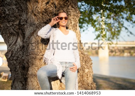 Young woman smiling and posing for a camera outdoors