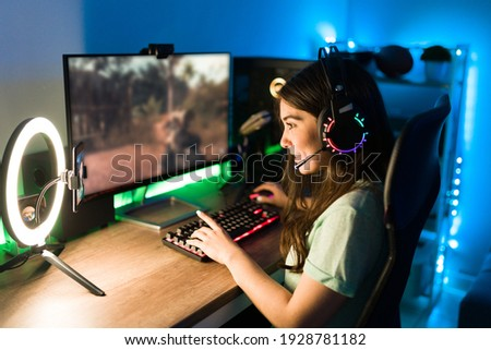 Young woman smiling and talking during a live stream on a smartphone with a ring light. Happy female gamer playing a video game in her computer with neon led lights Photo stock ©