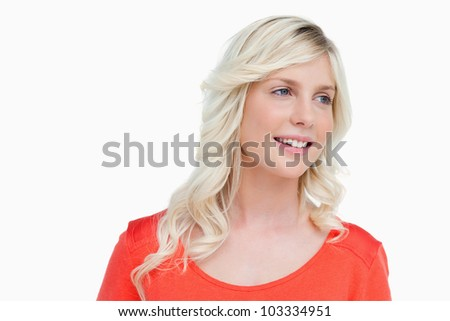 Young woman smiling as she looks to the side against a white background