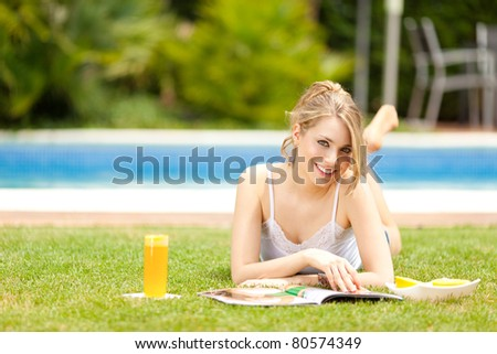 Young woman smiling drinking orange juice