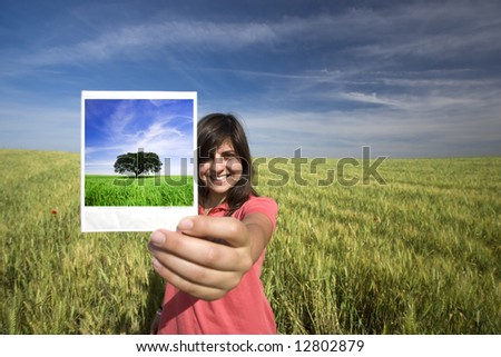 young woman smiling holding single instant photo film strip