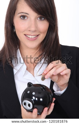 Young woman smiling putting coin in a piggy bank