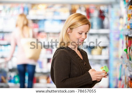 Young woman smiling while shopping in the supermarket with people in the background