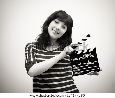 Young woman smiling with movie clapper board vintage black and white #324177890