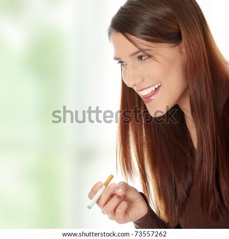 Young woman smoking electronic cigarette (e-cigarette)