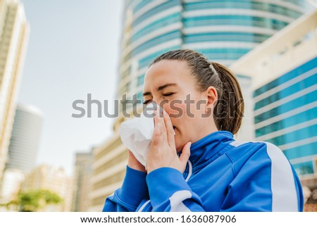 Young woman sneezes with allergies
