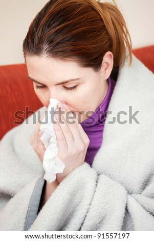 Young woman sneezing in the handkerchief