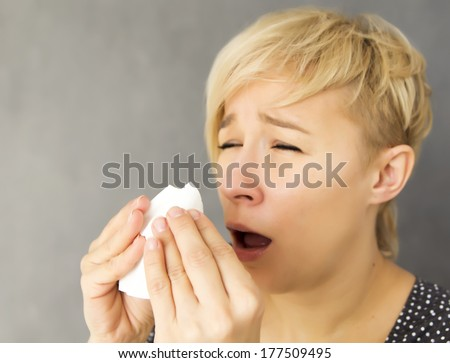 young woman sneezing into handkerchief