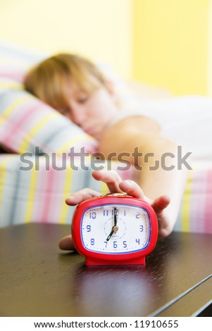 Young woman snoozing a red alarm clock
