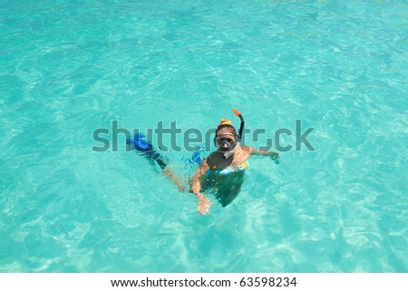 Young woman snorkeling in a tropical lagoon - stock photo