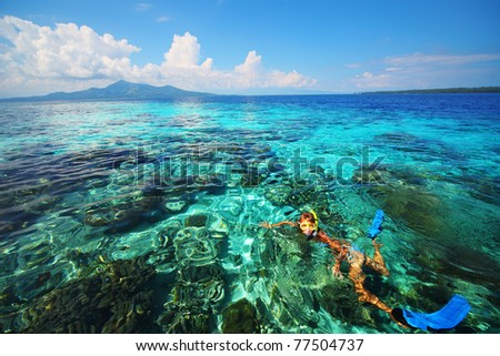 Young woman snorkeling in coral reef in tropical sea. Bunaken island. Indonesia