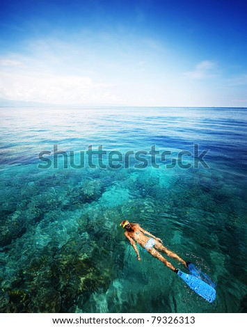 Young woman snorkeling in transparent shallow sea above coral reef.