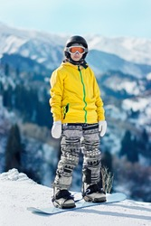 Young woman snowboarder in a yellow jacket and black helmet on the background of snowy mountains