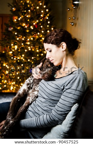 Young woman snuggling with her dog at Christmas time