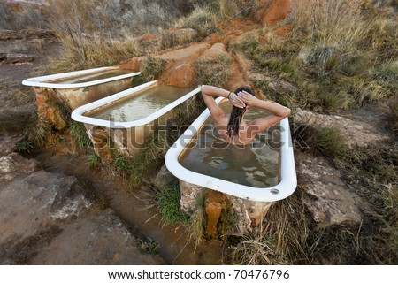 Young woman soaking in the rustic and funky Mystic Hot Springs,  the calcium rich water deposits create the organic textures flowing over the ground and into a recycled claw foot bathtub.