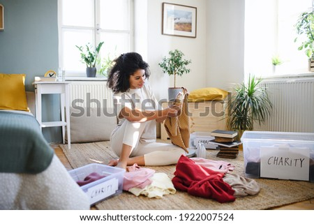 Young woman sorting wardrobe indoors at home, charity donation concept. Foto stock ©