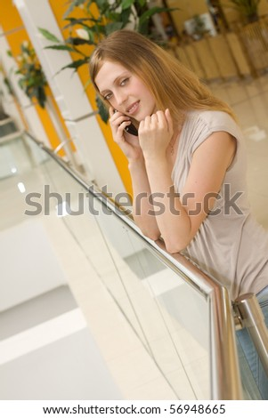 young  woman speaking on cellphone in shopping centre