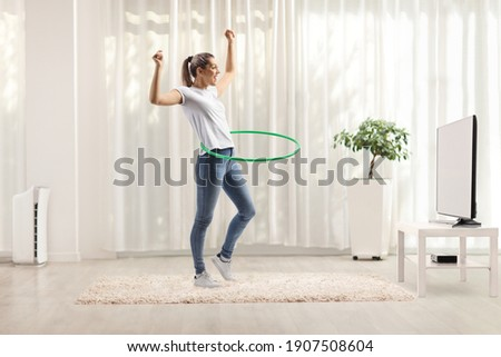 Young woman spinning hula hoop at home in a living room in front of tv