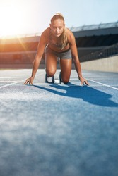 Young woman sprinter in the starter position on a race track at a sports stadium looking up at camera with determination. Runner on racetrack starting blocks.