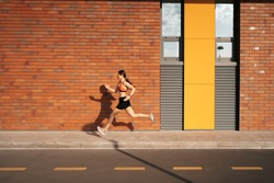 Young woman sprinting in the morning outdoors. Side view of female runner working out in the city.