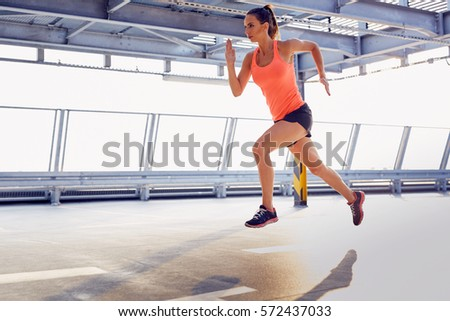 young woman sprinting on...