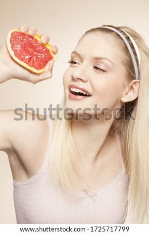 Young woman squeezing grapefruit, studio shot