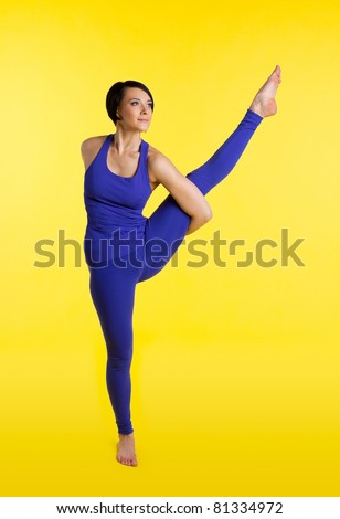 Young woman stand and take leg on hands