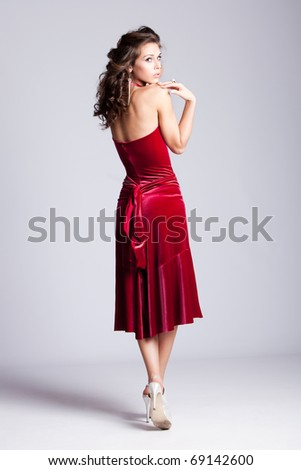 young  woman stand in red elegant dress, from back, full body shot, studio shot