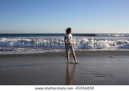 young woman stand  on beach with wonderful waves on ocean. Gran Canaria