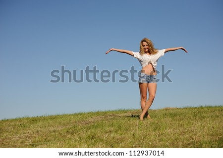 Young woman stand on the green summer field - stock photo
