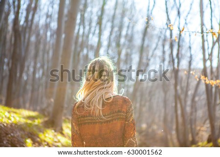 Young Woman standing alone outdoor with wild forest mountains on background Travel Lifestyle. Young blonde girl portrait walking in the forest. Girl in the forest.silhouette girl in the forest.  #630001562