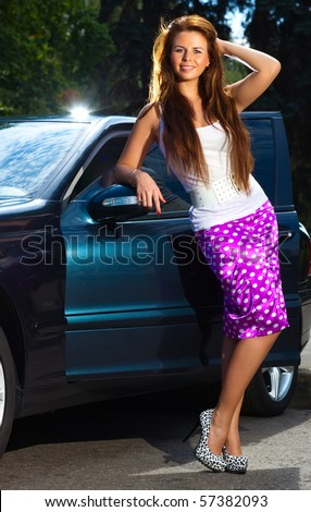 Young woman standing at her car.