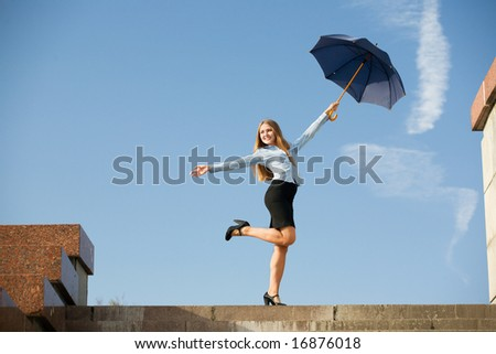 Young woman standing at steps with umbrella and smiling.