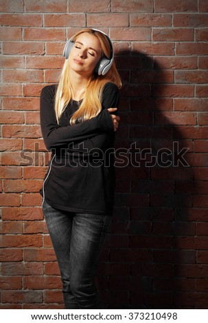 Young woman standing at the brick wall and listening to music #373210498