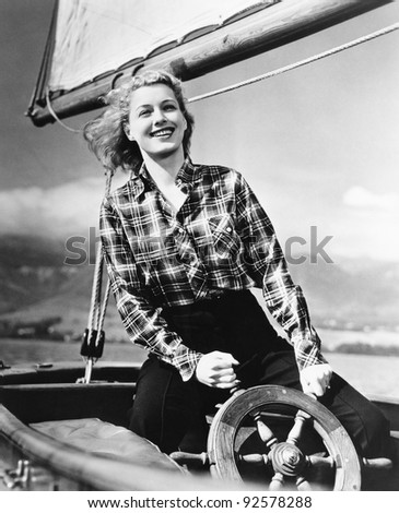 Young woman standing at the helm of a sailboat and holding the wheel