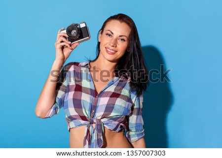 Young woman standing bare belly isolated on blue wall holding film camera looking camera smiling happy #1357007303