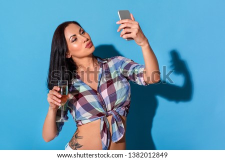 Young woman standing bare belly isolated on blue wall holding glass of champagne taking selfie photos on smartphone pouting lips to camera playful