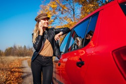 Young woman standing by car using smartphone, talking on mobile on autumn road. Driver stopped auto in forest to call