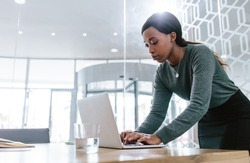 Young woman standing by conference table and working on laptop. Female preparing a business proposal before a meeting in boardroom.
