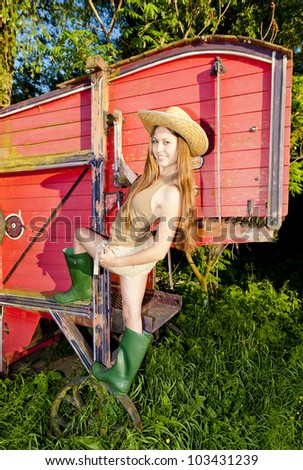 young woman standing by old threshing machine