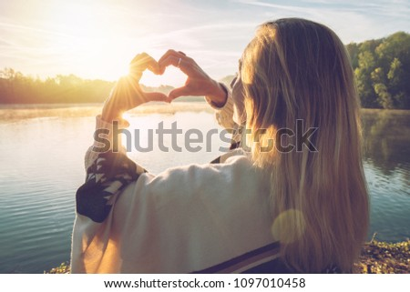 Young woman standing by the lake at sunrise making a heart shape finger frame on the beautiful landscape, reflection on water. People love travel