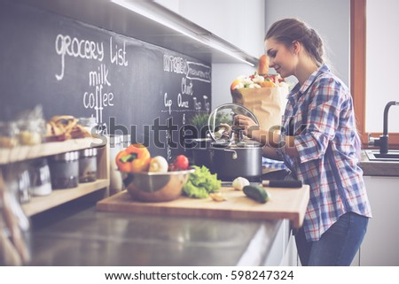 Shutterstock Young woman standing by the stove in the kitchen