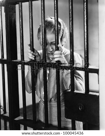 Young woman standing in a prison cell