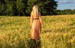 Young woman standing in a wheat field with sunrise on the background. Blonde in a pink dress.