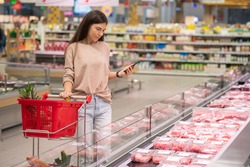 Young woman standing in aisle with shopping cart choosing fresh raw meat in modern supermarket