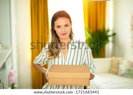young woman standing in her apartment and holding a cardboard box in  hands, reciving a new parcel, doing shopping online or sending some goods to the client directly from home
